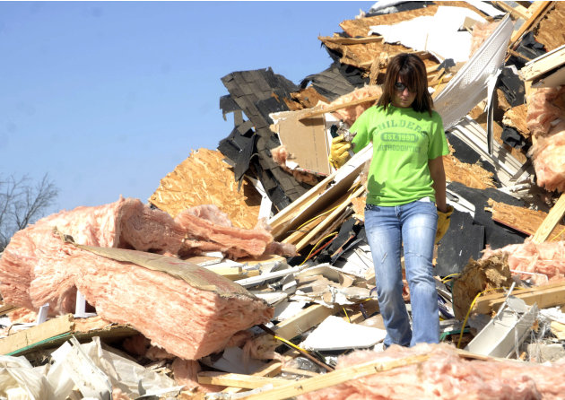 Cera Wise of Carrier Mill, Ill., searches for items in the rubble of a house that had blown across the road during Wednesday's tornado on Thursday, March 1, in Harrisburg, Ill. (AP Photo/The Southern