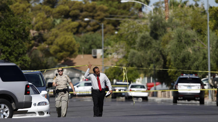 Authorities walk along a street near the scene of a home invasion in Las Vegas on Tuesday, July 29, 2014.Police say a suspect is dead and multiple people were wounded in a Las Vegas crime spree that included a carjacking and two home invasions. (AP Photo/Las Vegas Review-Journal, Erik Verduzco)