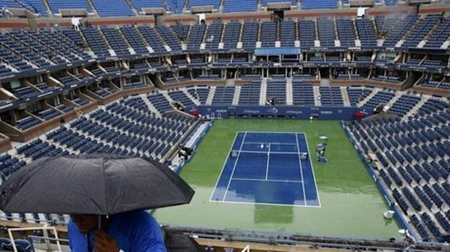 Tournament workers walk under umbrellas at Arthur Ashe Stadium after rain postponed play in the U.S. Open tennis tournament in New York, September 6, 2011