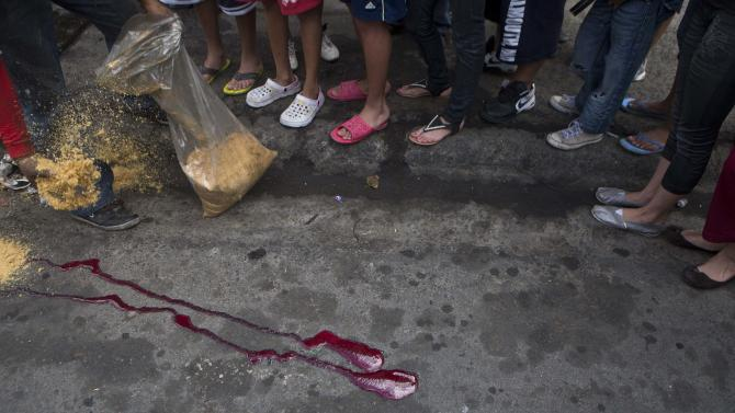 In this Monday, Dec. 1, 2014 photo, children watch a man use sawdust to cover blood spilled from a murder victim after the body was taken away by authorities, in Tegucigalpa, Honduras. In Honduras there where nearly 1,000 children killed this year and in the United States border authorities have arrested more than 8,000 Honduran children in 2014 as they tried to reunite with parents working there. (AP Photo/Esteban Felix)