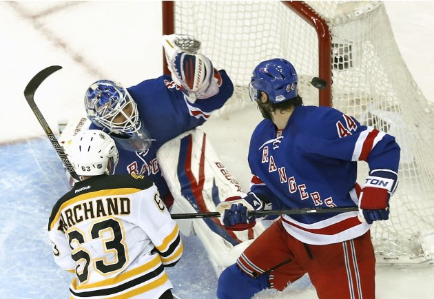 The puck hits the post as Bruins' Marchand and Rangers' Eminger jockey for position in front of Rangers' Lundqvist in Game 4 of their NHL playoff hockey series in New York