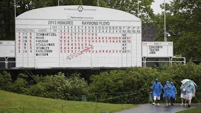 Golf fans walks past a leaderboard as play after play was suspended because of the weather during the second round of the Memorial golf tournament Friday, May 31, 2013, in Dublin, Ohio. (AP Photo/Darron Cummings)