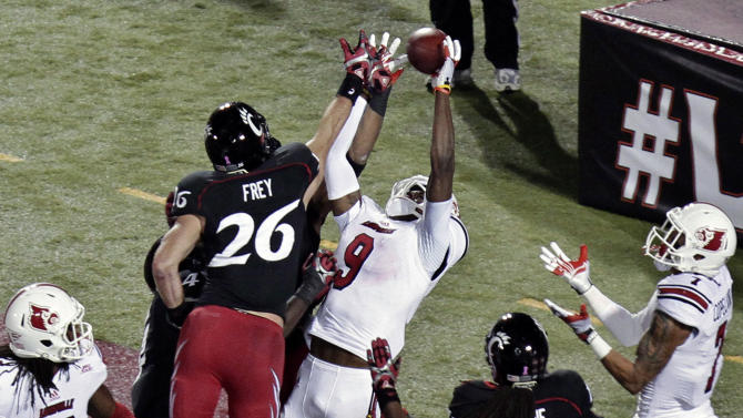Louisville wide receiver DeVante Parker (9) tries to pull in a pass in the end zone, while surrounded by Cincinnati defenders Drew Frey (26), Arryn Chenault, behind Frey, and Deven Drane (11) on the last play of the first half in an NCAA college football game in Louisville, Ky., Friday, Oct. 26, 2012. Parker could not hold on to the ball. At right is Louisville's Damian Copeland (7). (AP Photo/Garry Jones)