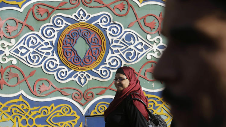 Egyptians walk in front of an Islamic motif outside of a shop in Cairo, Egypt, Friday, April 18, 2014. (AP Photo/Amr Nabil)