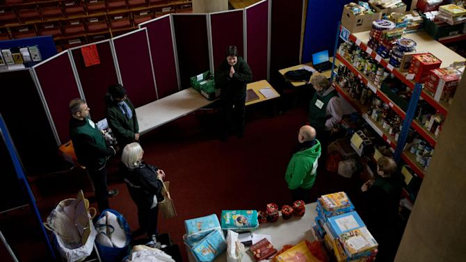 """In this photo taken Friday, April 5, 2013, Elizabeth Maytom, top center, the foodbank project leader for the Brixton and Norwood areas of London leads a group prayer with volunteers at the start of a distribution session at a food bank in St Luke's Church in the West Norwood area of London. It's possible that official figures on first quarter economic growth, to be released Thursday, could put the country back in recession. It would take the smallest statistical variation to put the figure in negative territory which would place the country in recession, another recession _ the third since the 2008 financial crisis _ and is already being referred to with foreboding in the media as a """"Triple Dip"""". (AP Photo/Matt Dunham)"""