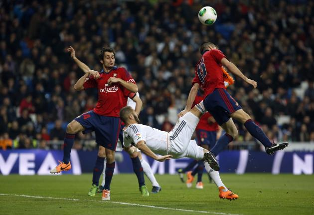 Real Madrid's Karim Benzema kicks the ball past Osasuna's Damia Abella and Oier Sanjurjo during their Spanish King's Cup soccer match at Santiago Bernabeu stadium in Madrid