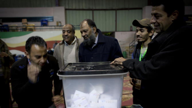 Egyptian election workers unseal a ballot box for counting at the end of the second round of a referendum on a disputed constitution drafted by Islamist supporters of president Mohammed Morsi at a polling station in Giza, Egypt, Saturday, Dec. 22, 2012. Egypt's Islamist-backed constitution headed toward likely approval in a final round of voting on Saturday, but the deep divisions it has opened up threaten to fuel continued turmoil. (AP Photo/Nasser Nasser)