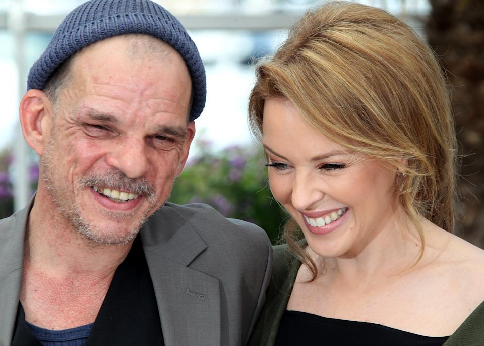 Actors Denis Lavant, left and Kylie Minogue pose during a photo call for Holy Motors at the 65th international film festival, in Cannes, southern France, Wednesday, May 23, 2012. (AP Photo/Joel Ryan)
