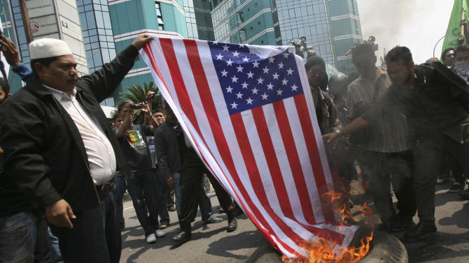 """Indonesian Muslims burn an American flag during a protest against an American-made film that ridicules Prophet Muhammad outside the U.S. Consulate in Medan, North Sumatra, Indonesia, Tuesday, Sept. 18, 2012. Indonesians continue to protest the anti-Islam film """"Innocence of Muslims,"""" torching the flag and tires outside the consulate in the country's third largest city of Medan. (AP Photo/Binsar Bakkara)"""