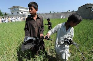 Pakistani children collect debris at the site of the…