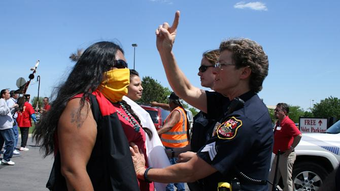 A Rapid City police officer stops a woman from crossing onto property belonging to Rapid City Regional Hospital Monday, May 21, 2012, in Rapid City, S.D. Hundreds of people have marched more than two miles from Memorial Plaza in Rapid City to a local hospital where a man says the letters KKK were carved into his stomach while undergoing surgery. (AP Photo/Kristi Eaton)