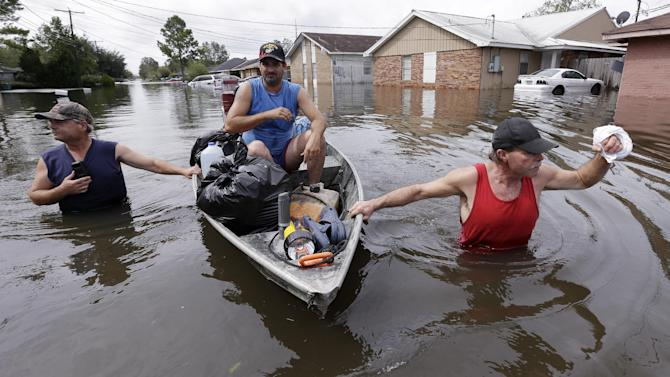 Christopher Tabb, left, with the help of Anthony Tabb, center, and friend, Frank Story, right, uses a boat to recover items from his flooded home, Friday, Aug. 31, 2012, in Reserve, La.  Isaac crawled into the central U.S. on Friday, leaving behind a soggy mess in Louisiana.  It will be a few days before the water recedes and people in flooded areas can return home. New Orleans itself was spared, thanks in large part to a levee system fortified after Katrina devastated the Gulf Coast in 2005. (AP Photo/Eric Gay)