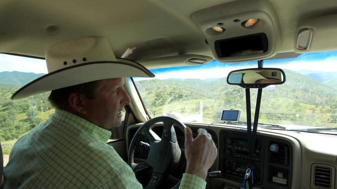 In this Friday, Aug. 10, 2012 photo, rancher Dan Bell, who leases a 35,000-acre cattle ranch along the border between the United States and Mexico, drives around as he checks out part of the property, in Nogales, Ariz. When Bell drives through the ranch, he speaks of the hurdles that the Border Patrol faces in his rolling green hills of oak and mesquite trees: The hours it takes to drive to some places, the wilderness areas that are generally off-limits to motorized vehicles, and the environmental reviews required to extend a dirt road. (AP Photo/Ross D. Franklin)