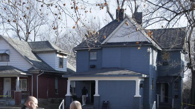 Investigators talks while standing across the street from a house where a man suspected of fatally shooting two police officers had stayed after the crimes, in Topeka, Kan., Monday, Dec. 17, 2012. The Kansas Bureau of Investigation identified the man who opened fire on Topeka police Cpl. David Gogian, 50, and Officer Jeff Atherly, 29, on Sunday night as 22-year-old David Tiscareno of Topeka. (AP Photo/Orlin Wagner)