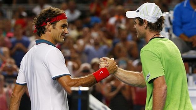Roger Federer of Switzerland (L) shakes hands with Blaz Kavcic of Slovenia after their men's singles match at the Australian Open 2014 tennis tournament in Melbourne January 16, 2014 (Reuters)