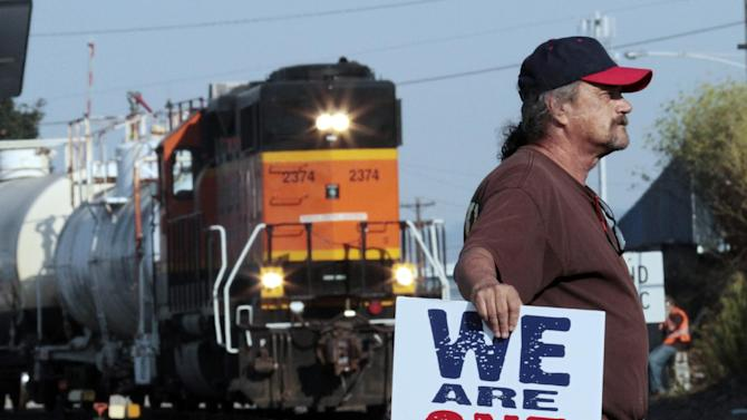 A man, who refused to identify himself, stands near railroad tracks while a train moves forward as a crowd of union workers and supporters gather at a crossing in Vancouver, Wash. Wednesday, Sept. 7, 2011. Hundreds of Longshoremen were at the crossing as part of an escalating dispute about labor at the EGT grain terminal at the Port of Longview, Wash.(AP Photo/Don Ryan)