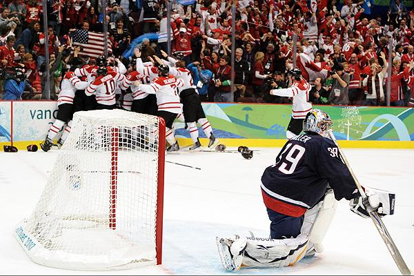 Ryan Miller slumps in his crease as Canada celebrates Sidney Crosby's gold medal-winning goal to beat Team USA in overtime at the 2010 Olympics in Vancouver