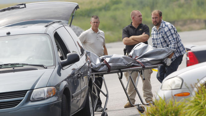 Police move the body of one of the victims to a van following a shooting in the parking lot of Jordan Manufacturing, Tuesday, Aug. 5, 2014, in Monticello, Ind. A northern Indiana sheriff says three people are dead following a shooting outside a furniture plant. (AP Photo/Journal & Courier, John Terhune)