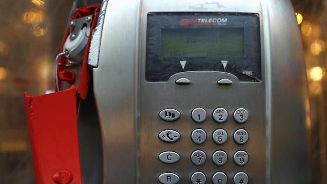 A broken Telecom Italia public telephone is pictured in downtown Milan