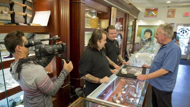 In this Wednesday, April 3, 2013, photo, cameraman Mark Matusiak shoots a scene between Chumlee, second from left, Corey Harrison, and customer Gene McCauliff of Las Vegas, for the reality tv series Pawn Stars, Wednesday, April 3, 2013, in Las Vegas. Pawn sales at the Gold & Silver Pawn Shop bring in about $20 million a year, up from the $4 million a year it made before the show aired.Turning small business owners into stars has become a winning formula for television producers, but the businesses featured in the shows are cashing in, too. Sales explode after just a few episodes have aired, transforming nearly unknown small businesses into household names. (AP Photo/Julie Jacobson)