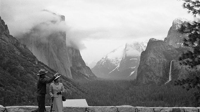 FILE - In this March 5, 1983 file photo taken by Walt Zeboski, park superintendent Bob Binnewies points out highlights from Inspiration Point to Queen Elizabeth II during her visit to Yosemite National Park, in California. Walt Zeboski, who chronicled Ronald Reagan's 1980 presidential campaign and a succession of California governors as a photographer for The Associated Press, has died. He was 83. (AP Photo/Walt Zeboski, File)