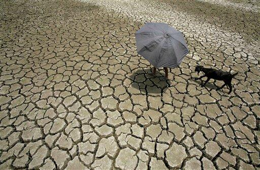 A village boy leads his goat past a parched pond on the outskirts of the eastern Indian city of Bhubaneswar, India, Thursday, May 17, 2012. Huge swathes of rural farmland has turned dry as farmers await the annual monsoon rains which, according to the India Meteorological Department, are expected to reach on time this year. (AP Photo/Biswaranjan Rout)
