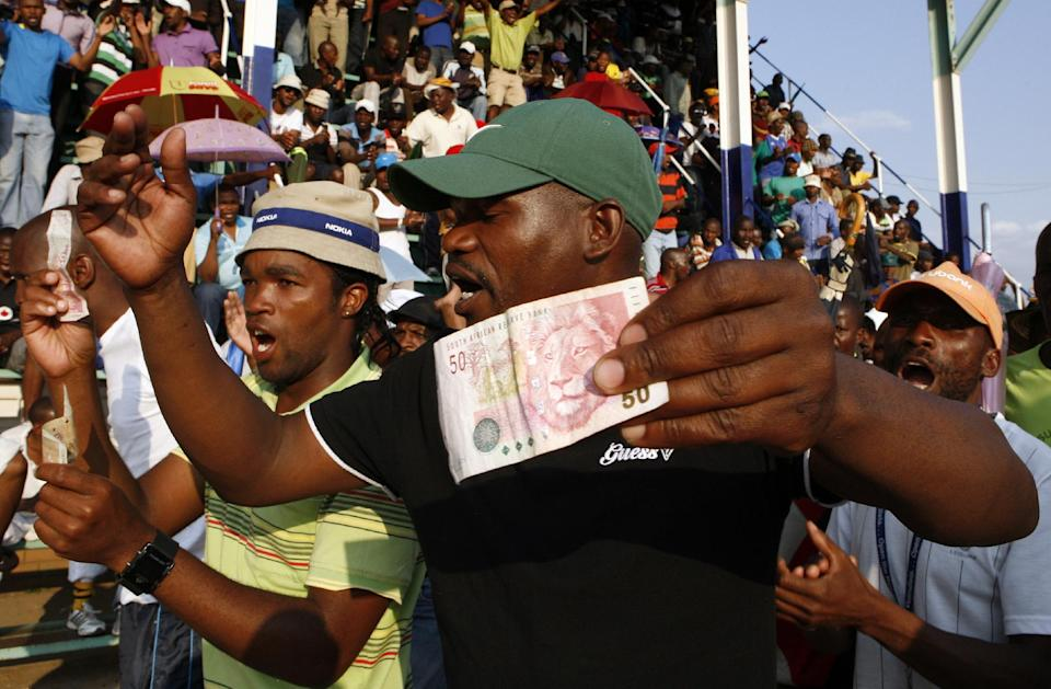 Miners sing and dance whilst holding South African bank notes in Lonmin Platinum Mine near Rustenburg, South Africa, Tuesday, Sept. 18, 2012. Striking miners have accepted a company offer of a 22% overall pay increase to end more than five weeks of crippling and bloody industrial action. (AP Photo/Themba Hadebe)