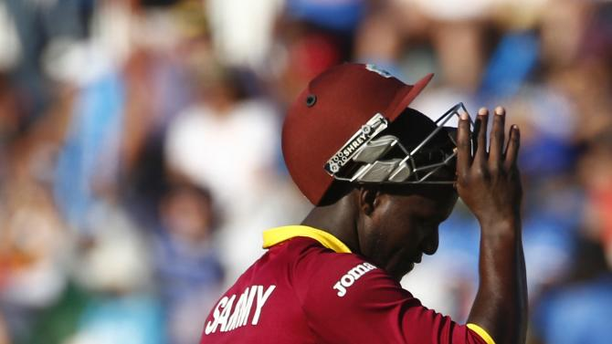 West Indies batsman Darren Sammy walks off the field after being caught behind by India's captain MS Dhoni during their Cricket World Cup match in Perth