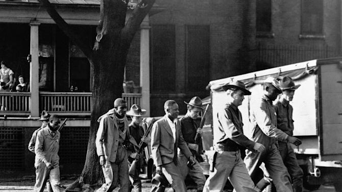 FILE - In this April 6, 1933 file photo, four of the Scottsboro Boys prisoners are escorted by heavily-armed guards into the Decatur, Ala., courtroom. Now that the Alabama Legislature is allowing posthumous pardons for the Scottsboro Boys, the nine African-American youths wrongfully convicted of raping two caucasian women more than 80 years ago, there is still much work to be done before their names are officially cleared. (AP Photo/File)