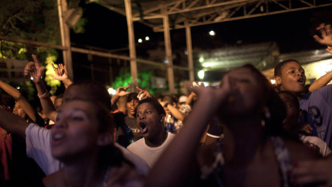 """In this Feb. 5, 2012 photo, people sing along during a funk """"baile"""" in the Tabajaras slum in Rio de Janeiro, Brazil. In the last five years, the genre has expanded its reach and enjoyed more social acceptance, with the help of an association of funk artists and supporters, Apafunk, and the backing of liberal legislators.  (AP Photo/Felipe Dana)"""