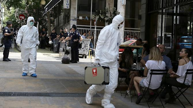 Police bomb disposal experts, in white clothes, search for evidence, near the central Athens offices of the Pan-Hellenic Socialist Movement, or PASOK party, in central Athens, on Sunday, May 25, 2014 . Two shots from an AK-47 assault rifle were fired against the socialist PASOK party headquarters early Sunday. No one was at the premises at the time and there were no injuries. Greeks vote Sunday for European Parliament and a second-round voting in local government polls. (AP Photo/Dimitris Messinis)