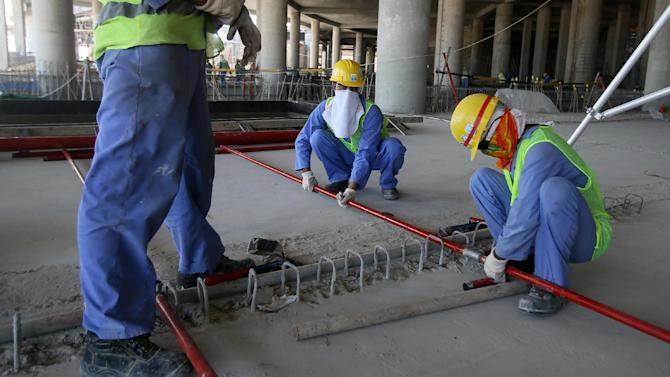Migrant labourers work on a construction site on October 3, 2013 in Doha in Qatar
