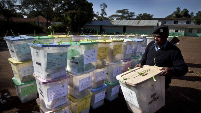 A police officer helps to carry ballot boxes for stacking prior to having their votes tallied, at a vote tallying center in Nairobi, Kenya Tuesday, March 5, 2013. With about a third of ballots counted provisional results showed Deputy Prime Minister Uhuru Kenyatta, who faces charges at the International Criminal Court, taking an early lead Tuesday as votes were counted the day after the country's presidential election. (AP Photo/Ben Curtis)