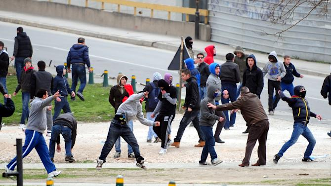 A group of ethnic Albanians throw stones at the police during a violent protest in Skopje, Macedonia, Saturday, March 2, 2013. Hundreds of ethnic Albanians staged a contra-protest on Saturday to express support for the designation of the new defense minister. Police said Saturday at least 20 people, from whom 13 police officers and other mainly youngsters were injured in a series of scuffles that erupted late on Friday and continued over night when a group of a few hundred Macedonians started a protest against the designation of a new defense minister Talat Xhaferi, an ethnic Albanian and former rebel commander. (AP Photo/Vangel Tanurovski)