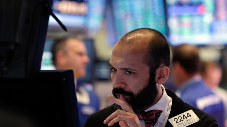 This Thursday, Feb. 28, 2013, photo shows specialist Fabian Caceres works at his post on the floor of the New York Stock Exchange. The stock market pushed higher Thursday afternoon, sending the Dow tantalizingly close to a record high. (AP Photo/Richard Drew)