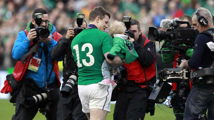 Ireland's O'Driscoll carries his daughter Sadie at the end of the Six Nations rugby union match against Italy at Aviva stadium in Dublin