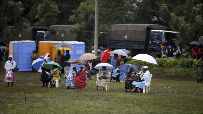 People take shelter from the rain as they attend a Mass celebrated by Pope Francis at the campus of the University of Nairobi, Kenya, Thursday, Nov. 26, 2015.  (AP Photo/Andrew Medichini)