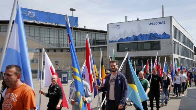 Volunteers carry flags in front of the Hallenstadion ahead of the opening ceremony of the 65th FIFA Congress in Zurich