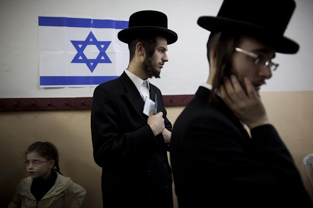 An Ultra-orthodox Jewish man holds his ID card as he waitS to vote in Bnei Brak, Israel, during legislative elections, Tuesday, Jan. 22, 2013.  Israelis began trickling into polling stations Tuesday m