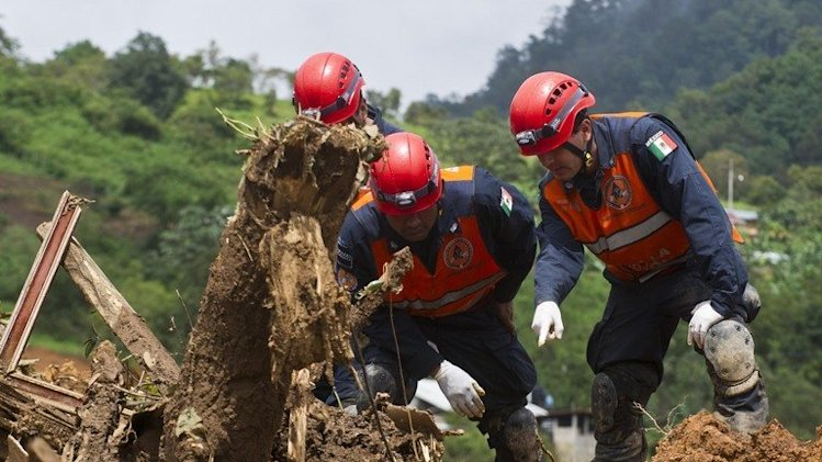 Mexican Federal Police search for bodies on the site of a landslide in La Pintada, Guerrero state, on September 19, 2013