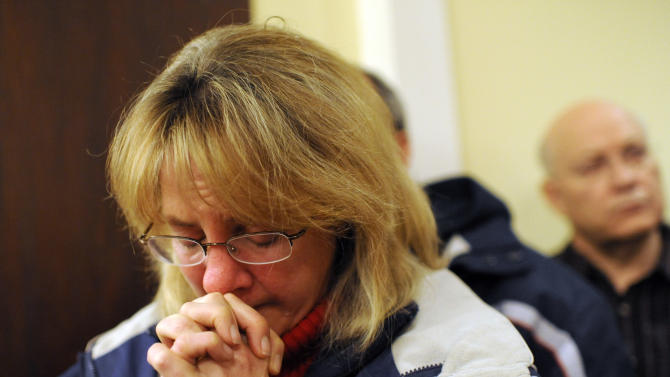 A mourner bows her head inside the St. Rose of Lima Roman Catholic Church at a vigil service for victims of the Sandy Hook Elementary School shooting, in Newtown, Conn. Friday, Dec. 14, 2012.  (AP Photo/Andrew Gombert, Pool)