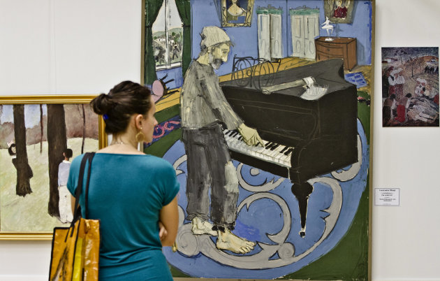 A picture taken Thursday, Sept. 27, 2012, shows a woman visiting an exhibition of visual art created by Romanian artists during the Communist period, between 1950 and 1990, in Bucharest, Romania. Opposed to the typical works used as a propaganda tool to glorify late Communist dictator Nicolae Ceausescu, the new exhibit of some 650 paintings, unveiled Thursday evening at the National Library, seeks to show that painters were not solely guided by politics, in an effort to restore pride in the nation's cultural heritage.(AP Photo/Vadim Ghirda)