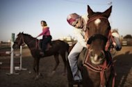 Palestinian women ride horses at the Al-Faisal riding centre in Gaza City on January 10, 2012. Horse riding has become a popular hobby in the Gaza Strip but local Palestinians face constant hurdles -- from a conservative society to Israel&#39;s blockade on the territory -- to practise the sport on their home turf