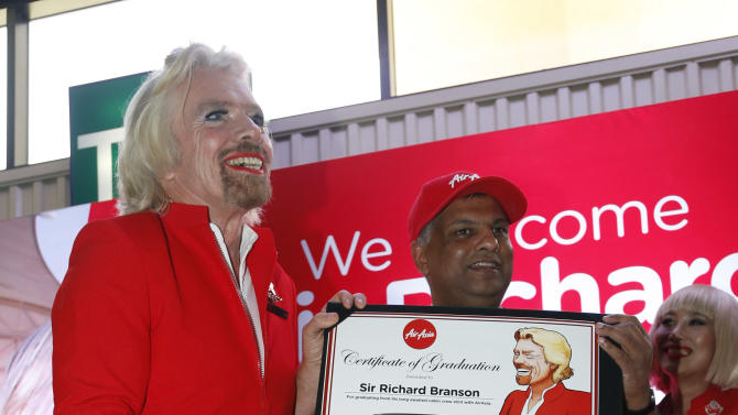 British entrepreneur Richard Branson, left, poses with AirAsia's Chief Executive Tony Fernandes while dressed as an AirAsia flight attendant  at a low cost carrier terminal in Malaysia, Sunday, May 12, 2013.  Branson wore the costume during his flight from Australia to Malaysia after losing a bet with Fernandes on which of their 2010 Formula One racing car teams would finish ahead of the other.  (AP Photo/Vincent Thian)