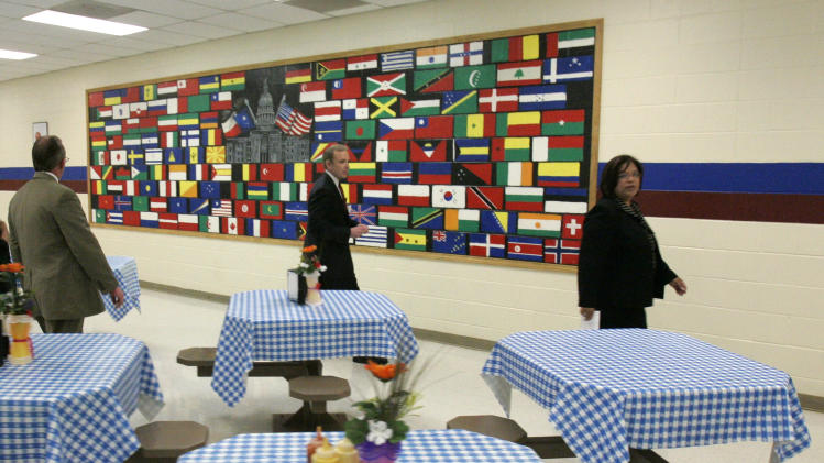 FILE- In an April 22, 2008 file photo, U.S. Immigration and Customs Enforcement officials, Marc Moore, left, and Gary Mead, center, along with Corrections Corporation of America Administrator, Evelyn Hernandez, right, talk about a mural of flags as well as the table cloths and flowers added to the cafeteria at the T. Don Hutto Residential Center in Taylor, Texas, during a tour for the media.  The U.S. is locking up more illegal immigrants than ever before, generating a lucrative business for the nation's largest prison companies. (AP Photo/Donna McWilliam, Pool, File)