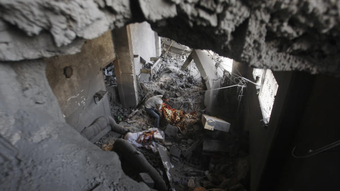 Palestinians inspect the rubble in a house destroyed on Sunday by an Israeli strike in Gaza City, Monday, Nov. 19, 2012. The Palestinian civilian death toll mounted Monday as Israeli aircraft struck densely populated areas in the Gaza Strip in its campaign to quell militant rocket fire menacing nearly half of Israel's population. (AP Photo/Hatem Moussa)
