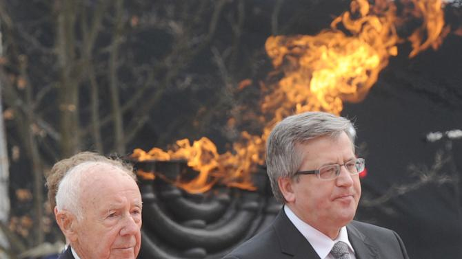 Polish President Bronislaw Komorowski, right, and Simha Rotem, one of the last living Warsaw Ghetto insurgents,  walk in front of the Warsaw Ghetto Uprising memorial, during the revolt anniversary ceremonies in Warsaw, Poland, Friday, April 19, 2013. Sirens wailed and church bells tolled in Warsaw as largely Roman Catholic Poland paid homage Friday to the Jewish fighters who rose up 70 years ago against German Nazi forces in the Warsaw ghetto uprising. (AP Photo/Alik Keplicz)