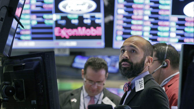 Specialist Fabian Caceres works at his post on the floor of the New York Stock Exchange Tuesday, Oct. 9, 2012. Another dire prediction about global economic growth is sending stocks lower on Wall Street in early trading. (AP Photo/Richard Drew)