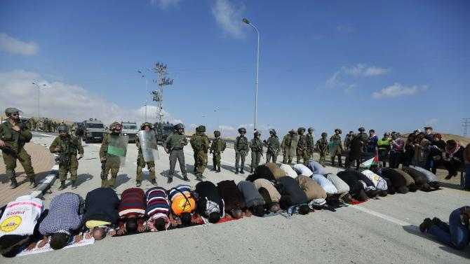 Palestinian protesters pray as Israeli soldiers and border policemen stand guard during a protest against Jewish settlements, near the West Bank city of Jericho