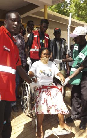 A woman injured in a grenade attack at the Utawala Inter-denominational church is helped by medical staff in Garissa, northern Kenya, Sunday, Nov. 4, 2012.  The Kenya Red Cross says at least 10 people were wounded in the grenade attack. (AP Photo/Daud Yusuf)